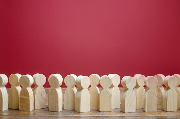 Een menigte van houten figuren van mensen. maatschappij, demografie. klanten en kopers
