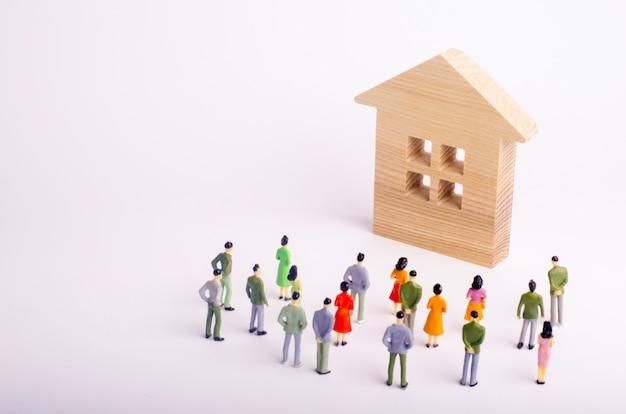 Een menigte van mensen die zich en een houten huis bevinden bekijken.