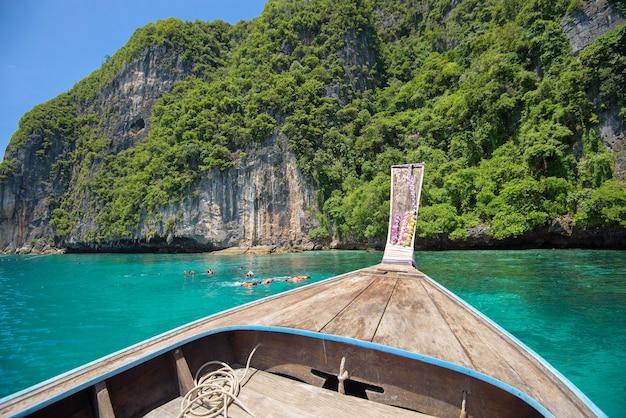 Een mening van thaise traditionele longtailboot terwijl toeristen snorkelen en duiken in de oceaan, phi phi-eilanden, thailand