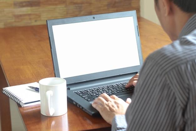 Een mens die computer met notitieboekje en witte mok op de houten lijst gebruikt.