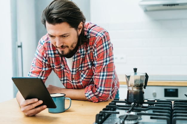 Een mens die op keukenteller leunt die slimme telefoon bekijkt