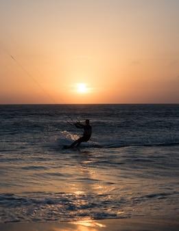 Een mens die vlieger uitoefent die bij zonsondergang in het strand van spanje surft