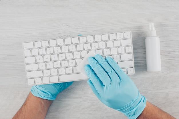 Een mens in handschoenen die een toetsenbord op lichte houten achtergrond met desinfecterend middel ontsmetten.
