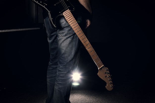 Een mens in jeans die zijn elektrische gitaar op zwarte achtergrond houdt