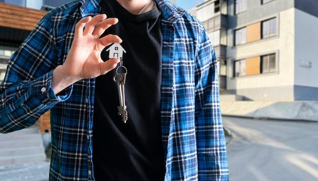 Een menselijke hand met een sleutel van huis symbool van de aankoop van appartement onroerend goed