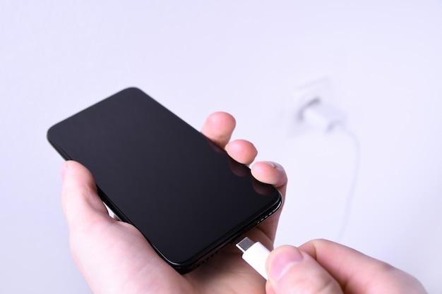 Een menselijke, mannelijke hand laadt de batterij mobiele slimme telefoon, mobiele telefoon, mobiel op het witte met een aansluiting in het frame.