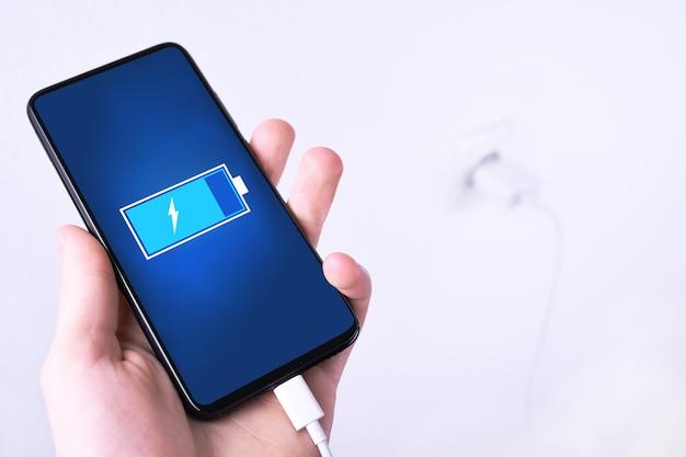 Een menselijke, mannenhand legt de batterij mobiele slimme telefoon op