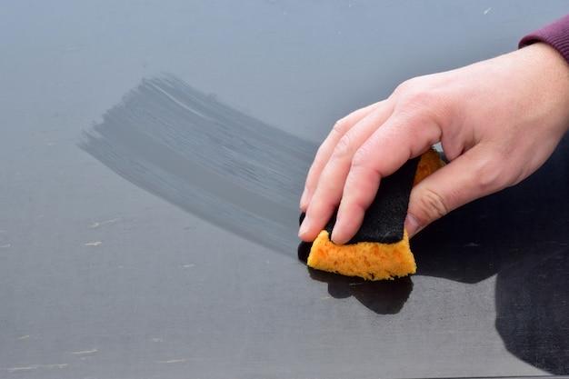 Een menselijke mannenhand veegt een vuil oppervlak af met een doek. daarna blijft er een schoon gewassen spoor achter