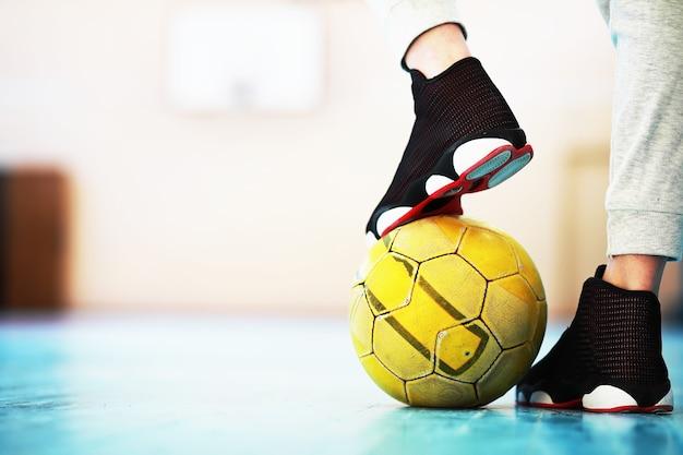Een menselijke voet rust op de voetbal op betonnen vloer. foto van een voetbal en sneakers in een houten vloer.