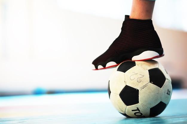 Een menselijke voetsteun op de voetbal op betonnen vloer foto van een voetbal