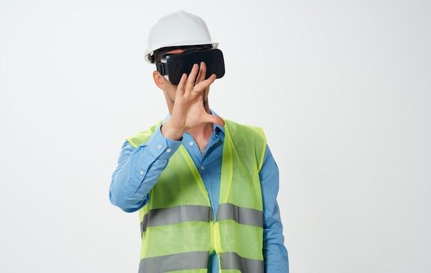 Een mensenbouwer in een geel vest en een witte helm met een rol papier in zijn hand reparatiewerkzaamheden.