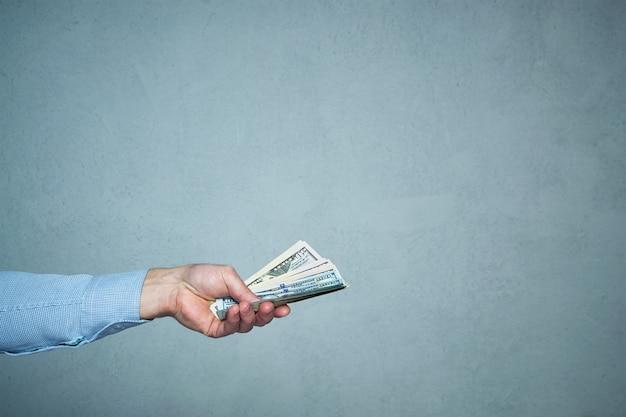Een mensenhand die geldclose-up geeft. bedrijfs- en investeringsconcept