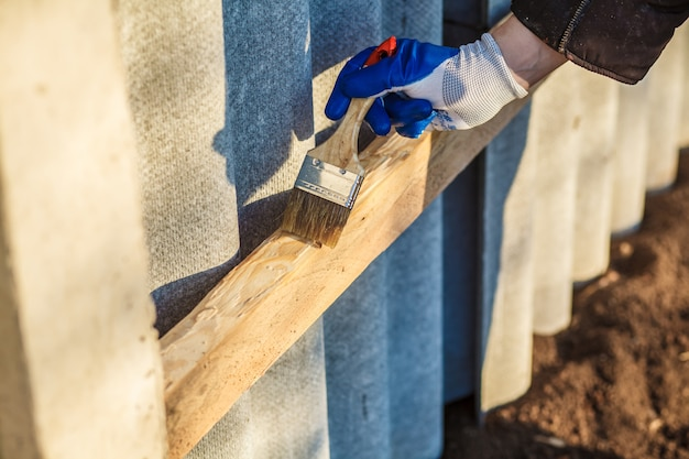 Een mensenhand met blauwe de verfborstel die van de handschoenholding houtlak toepast