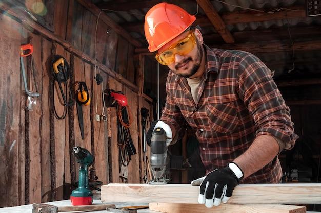 Een mensentimmerman snijdt een houten straal gebruikend een elektrische figuurzaag, mannelijke handen met een elektrische figuurzaagclose-up.
