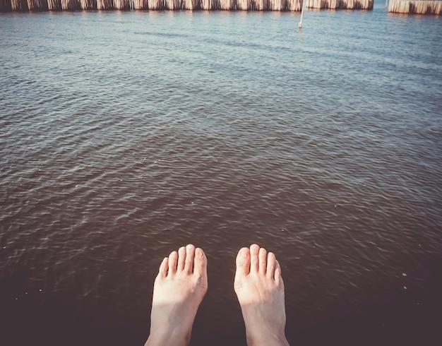 Een mensenvoet in de stroomlijn van diep donker water. de natuur aanraken. natuurgenezing concept idee