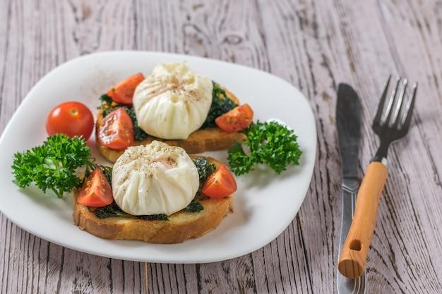 Een mes en vork en twee sneetjes gebakken brood met gepocheerde eieren op een houten tafel. vegetarische snack met gepocheerde eieren.