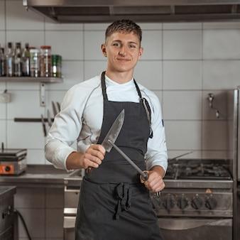 Een mes slijpen door een jonge chef-kok in de keuken