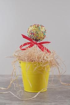 Een met lint versierd lolly en een klein hoopje stro in een emmer op marmer Gratis Foto