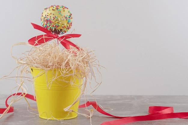 Een met lint versierd lolly en een klein hoopje stro in een emmer op marmer