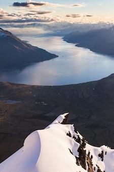 Een met sneeuw bedekte rotsvinger wijst naar queenstown en lake wakatipu, queens drive, remarkables, nieuw-zeeland