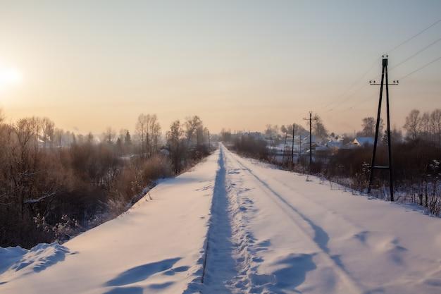 Een met sneeuw bedekte spoorweg en een pad dat in de winter door mensen erop wordt bewandeld. veel sneeuw.