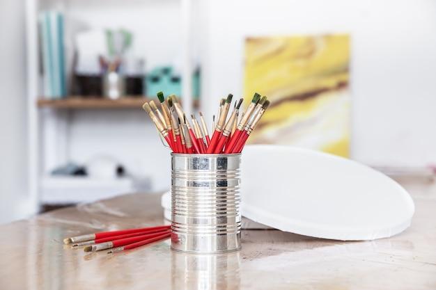 Een metalen blik met een set penselen om te schilderen in een kunstatelier