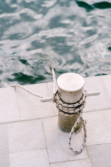 Een metalen chromen zeepaal op een stenen pier in de buurt van de zee