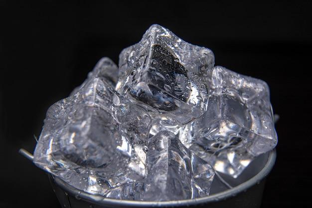 Een metalen emmer champagne vol ijs met een druppel water