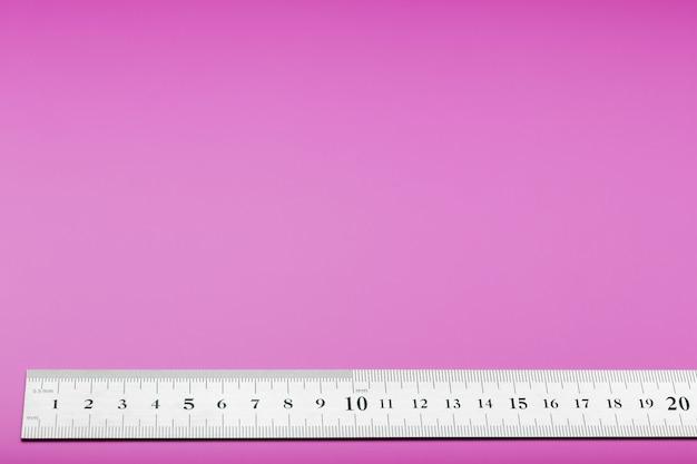 Een metalen liniaal met een schaal op roze is een superscape