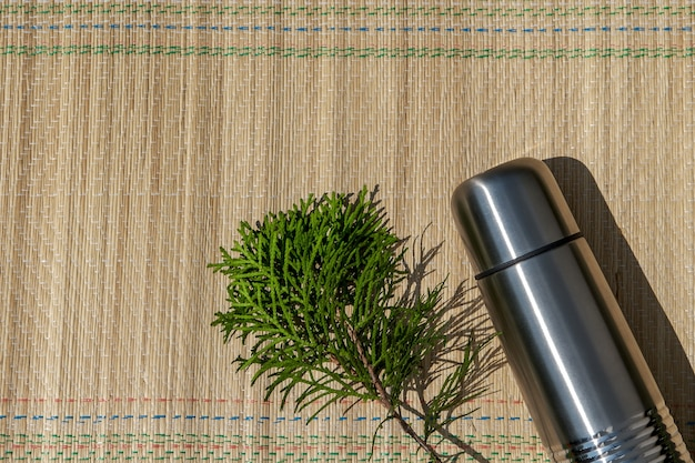 Een metalen thermoskan en een thuja-tak liggen op een bamboe-toeristenmat in de zon, flatlay-stijl.