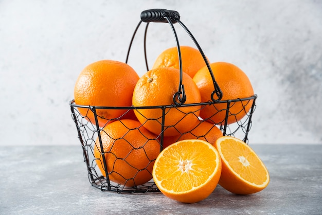 Een metallic zwarte mand vol sappig oranje fruit op stenen tafel.