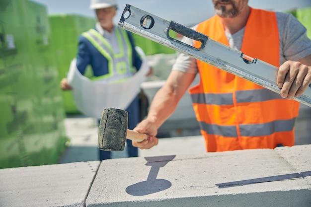 Een metselaar en een civiel ingenieur werken samen op een bouwplaats