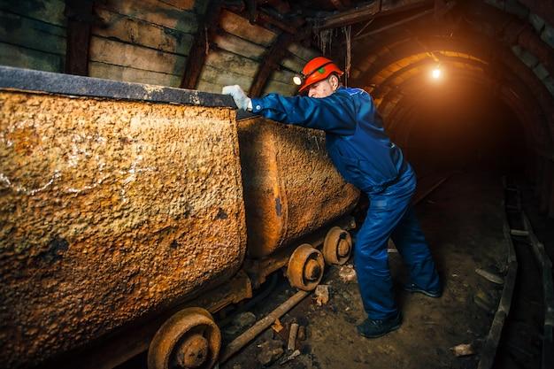Een mijnwerker in een kolenmijn staat in de buurt van een kar.
