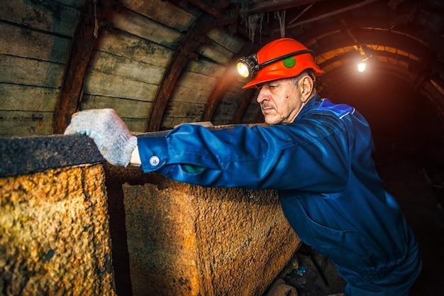 Een mijnwerker in een kolenmijn staat in de buurt van een trolley. ruimte kopiëren.