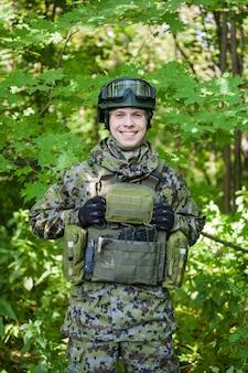Een militair in het bos met een machinegeweer in vredestijd. het leger voorbereiden op vijandelijkheden.