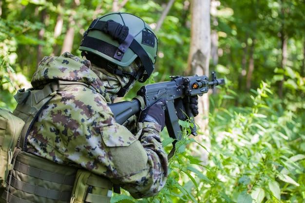 Een militair in het bos tijdens de oefening. soldaat machinegeweer en kleren