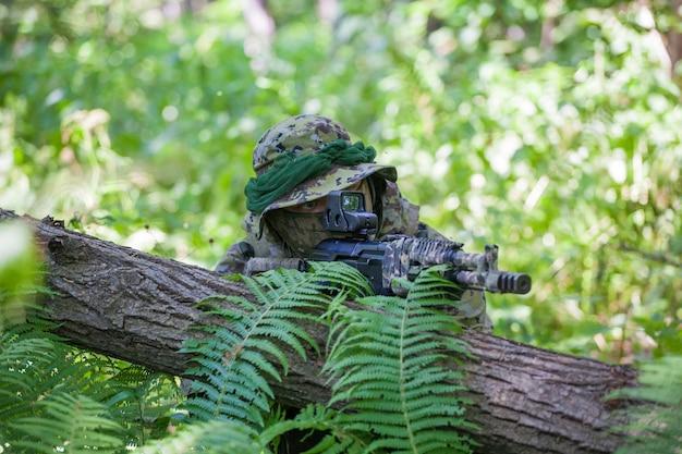 Een militair in het bos zit in een hinderlaag. soldaat machinegeweer en kleren