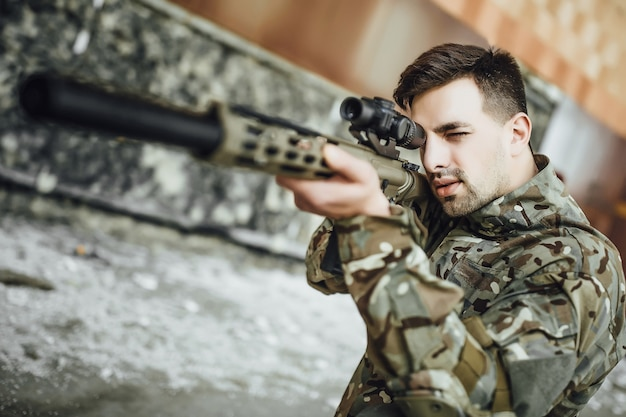Een militaire soldaat richt en houdt een groot geweer vast in het gebouw.