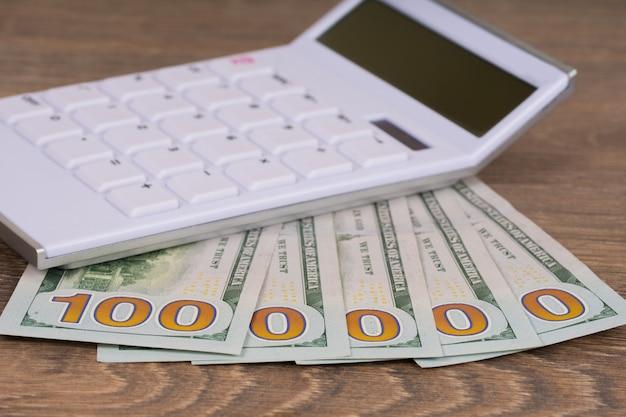 Een miljoen dollar en rekenmachine op houten tafel