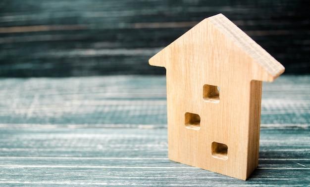 Een miniatuur drie verdiepingen tellende houten huis op een blauwe achtergrond. minimalisme. hypotheek