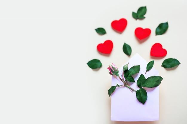 Een miniatuur roze bloem met bladeren en harten ligt in een envelop. valentijnsdag concept.