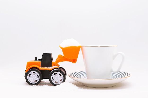 Een miniatuur speelgoedtractor die kristalsuiker in een beker ploegt