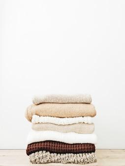 Een minimale stapel warme mooie vrouwelijke truien of pullovers liggend op een houten tafel