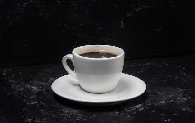 Een minimalistisch concept van een kopje koffie en dat staat op een zwarte abstracte achtergrond.