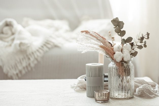 Een minimalistische compositie in de scandinavische stijl met droogbloemen in een vaas en kaarsen.