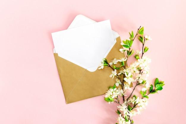 Een minimalistische platliggende compositie met een mock-up van een witte blanco briefkaart voor tekst, een envelop van kraftpapier, een pen, een tak bloeiende kers met bloemen op een roze achtergrond. bovenaanzicht.