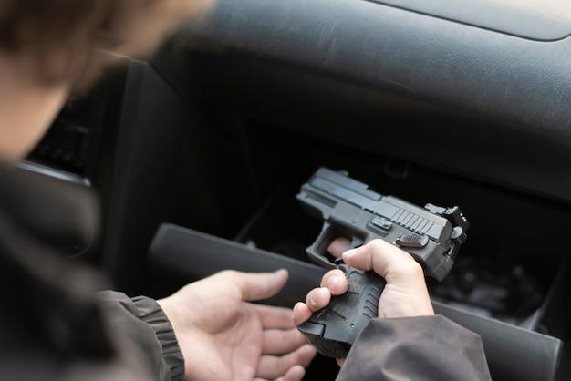 Een misdaadconcept, inbreker die het pistool pakt en een moord plant