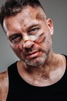 Een mishandelde man in een zwart t-shirt die eruitziet als een drugsverslaafde en een dronkaard staat tegen een grijze achtergrond