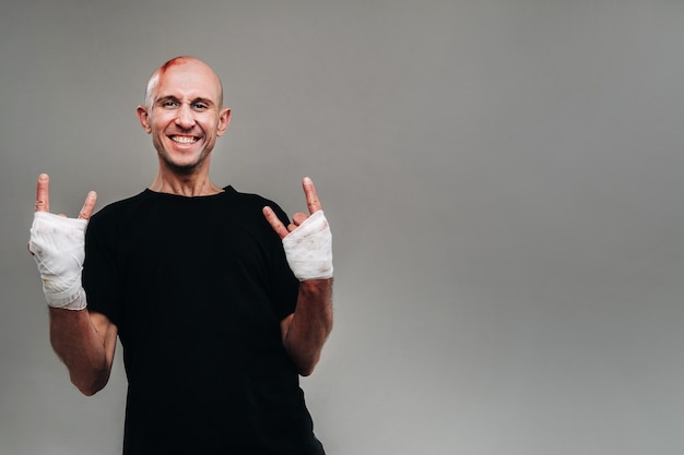 Een mishandelde man met zijn handen gewikkeld in een zwart t-shirt op een grijze achtergrond, eruitziend als een drugsverslaafde en een dronkaard.