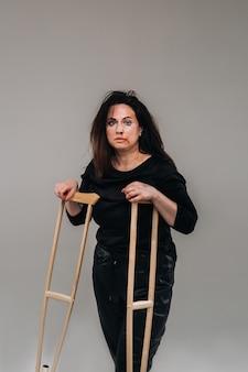 Een mishandelde vrouw in zwarte kleding met zwenkwielen in haar handen op een grijze achtergrond.